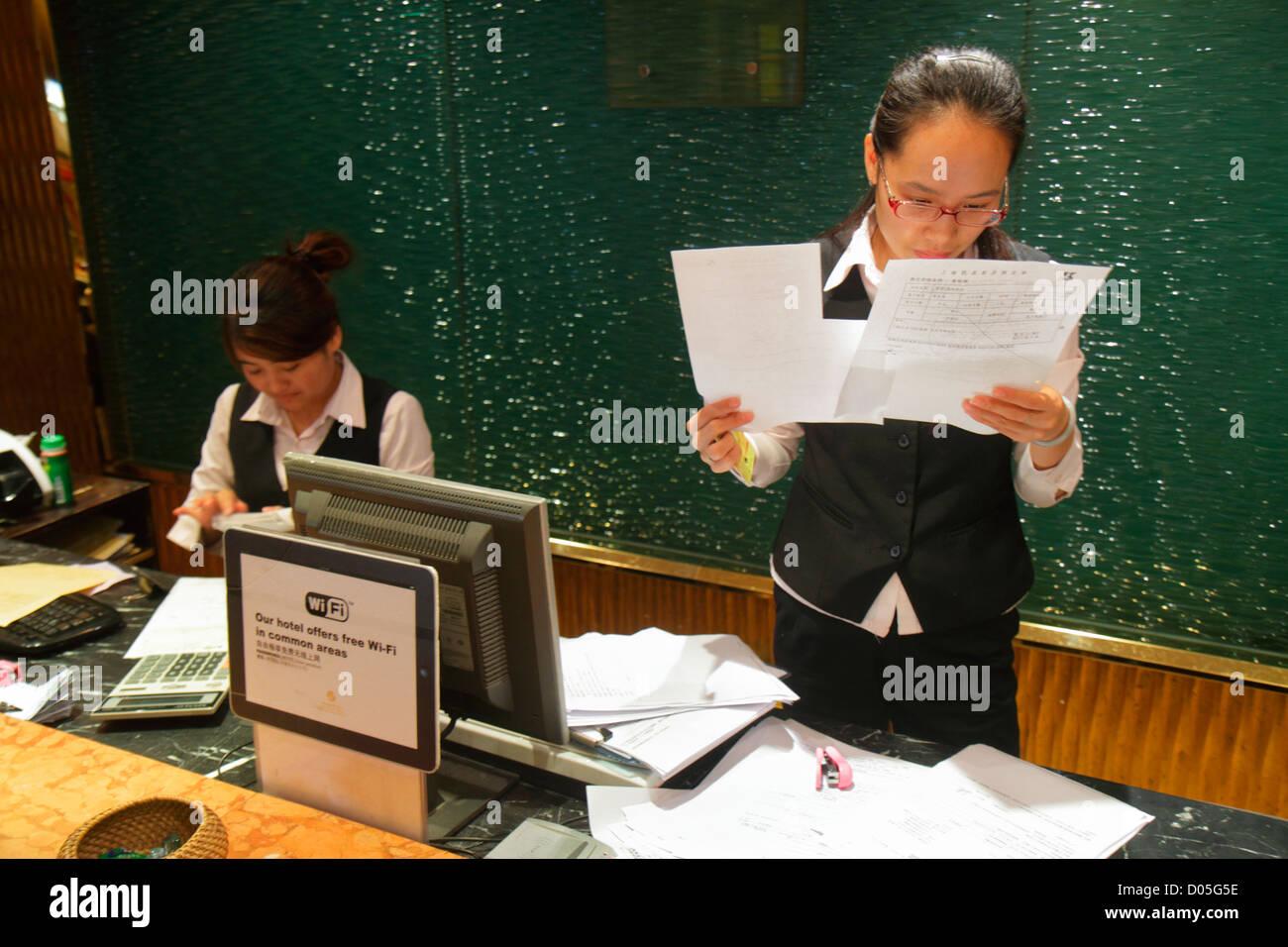 Shanghai China Dianchi Road Huangpu District Manhattan Bund Business Hotel lobby Asian woman front desk clerk employee - Stock Image