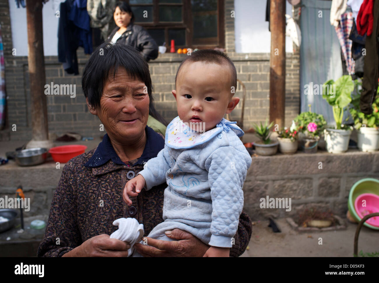 An elder lady holds a little boy at a courtyard in Laofen village, Pingshan county, Hebei, China. 23-Oct-2012 - Stock Image