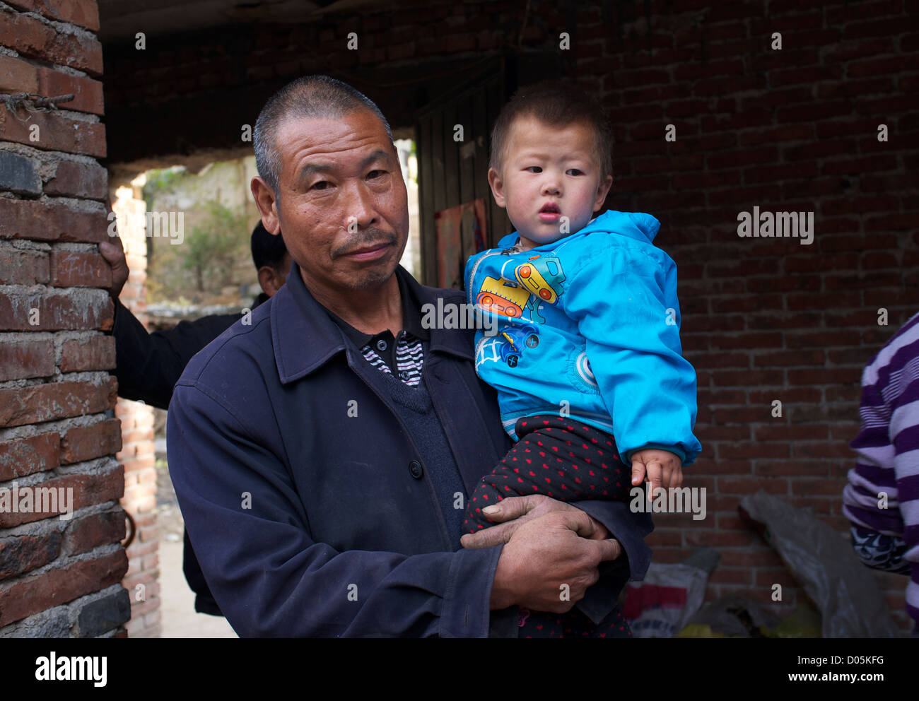 An elder man holds a little boy at a courtyard in Laofen village, Pingshan county, Hebei, China. 23-Oct-2012 - Stock Image