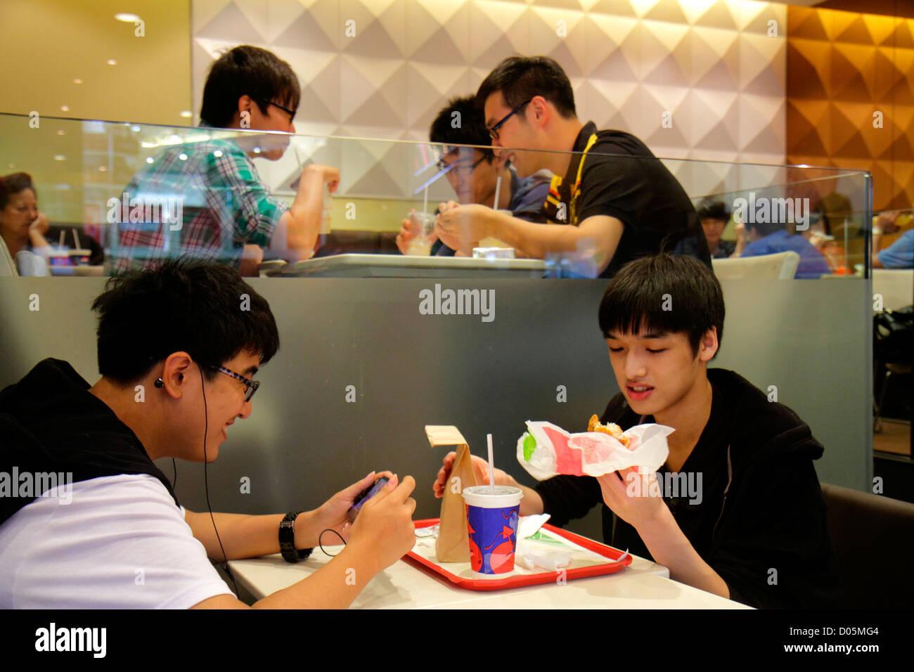 Shanghai China Huangpu District Xizang Road People's Square Raffles City shopping Asian teen boy eating US company - Stock Image