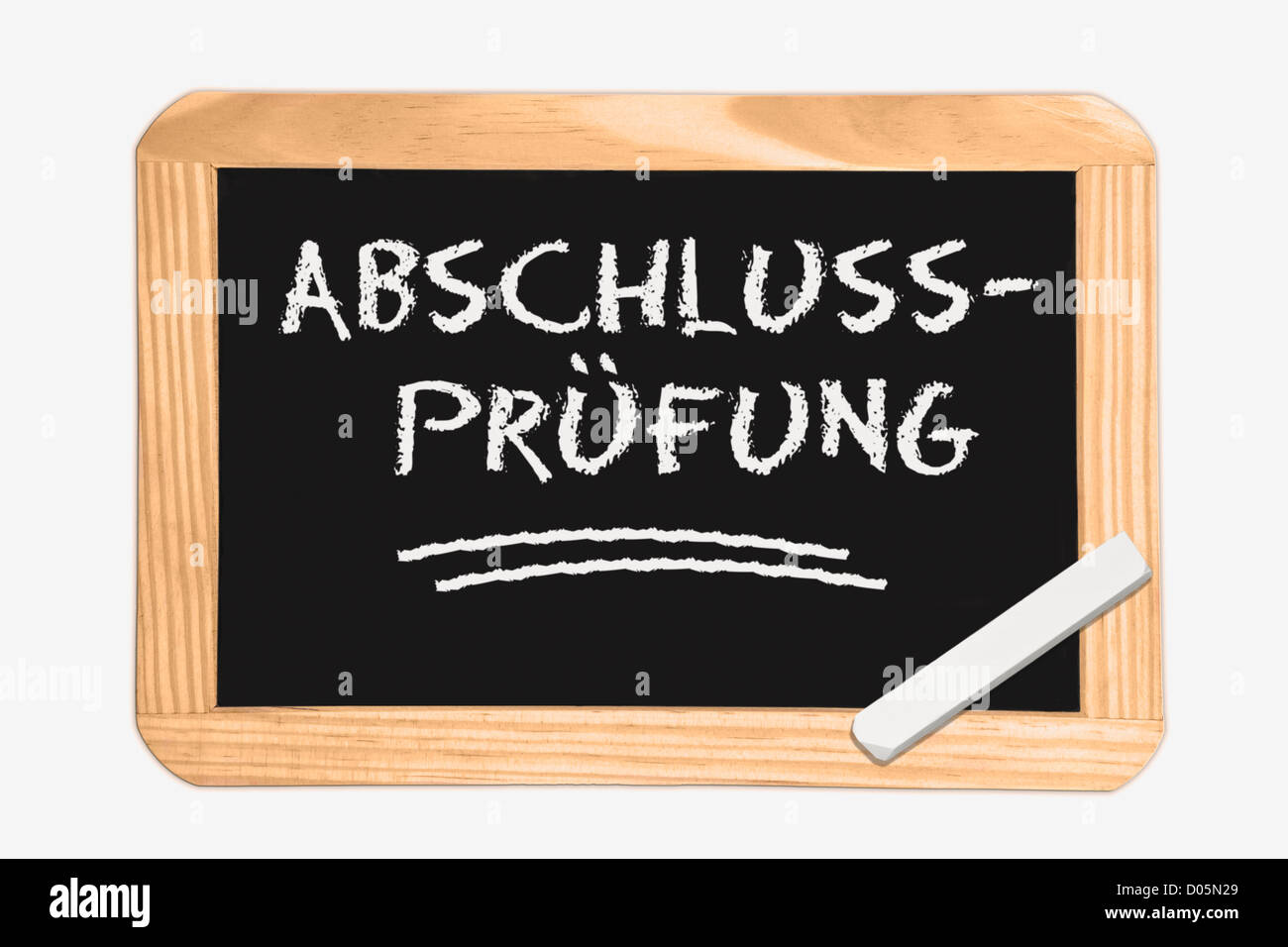 Detail photo of a Chalkboard with the German inscription final examination, white chalk lies in a corner - Stock Image
