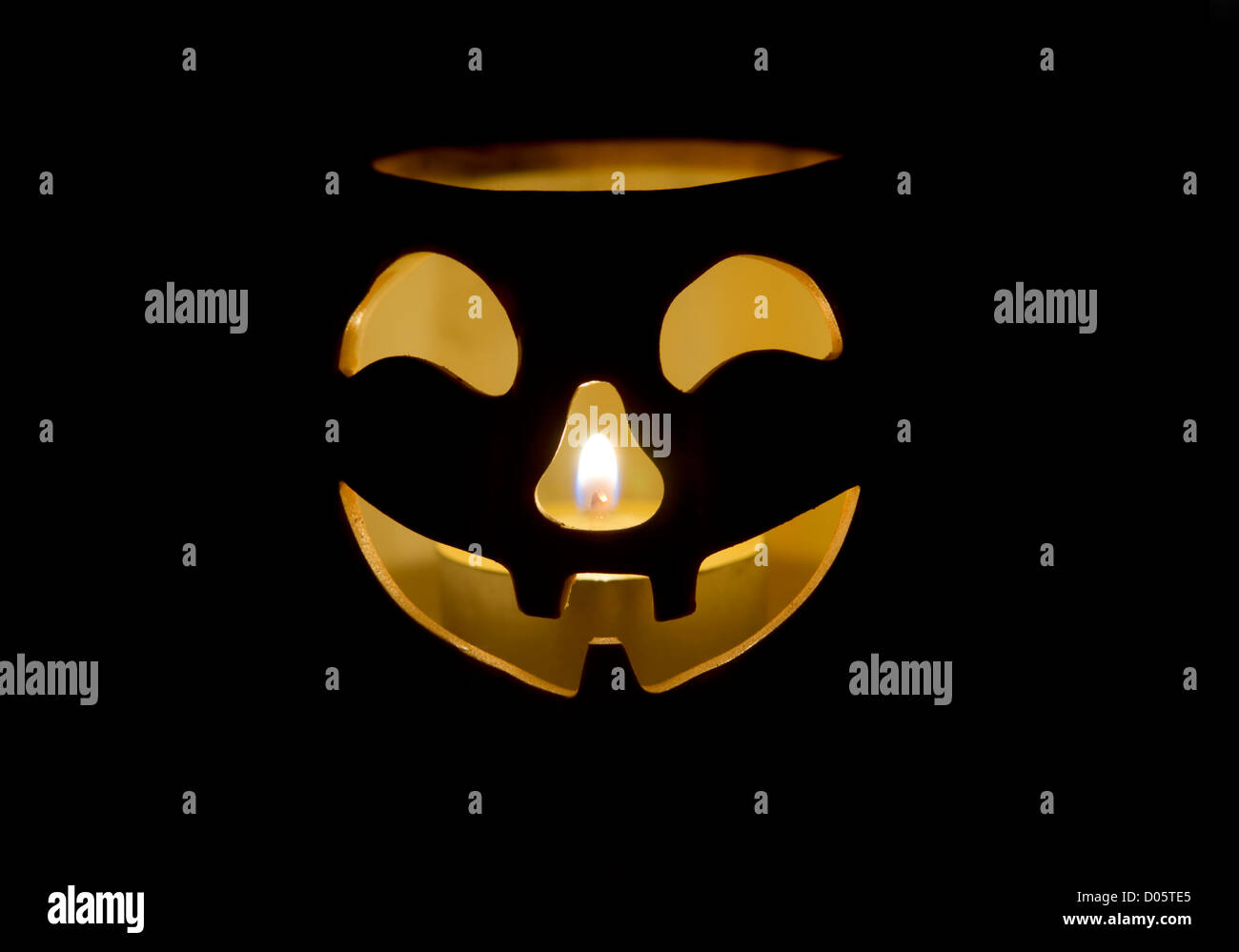 Halloween face pumpkin decoration lit with candle - Stock Image