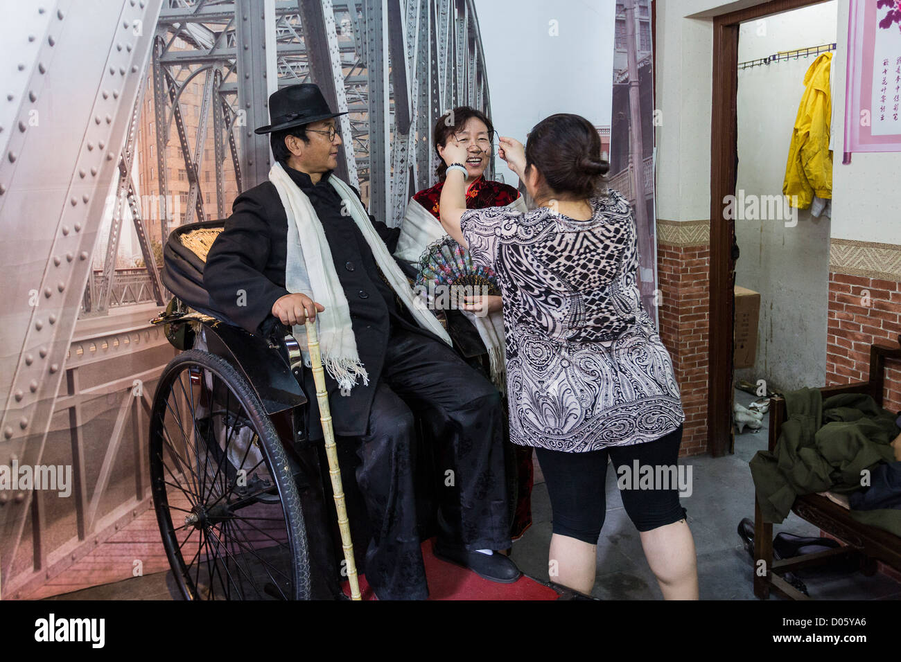 A Chinese man dresses in costume at a photo studio in Yu Gardens bazaar Shanghai, China - Stock Image
