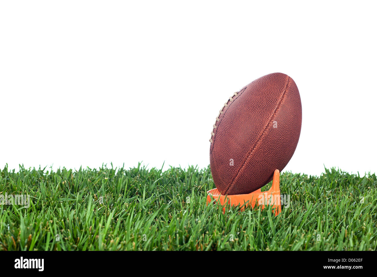 Football tee on green grass waiting for a kick off. White background for placement of copy. - Stock Image