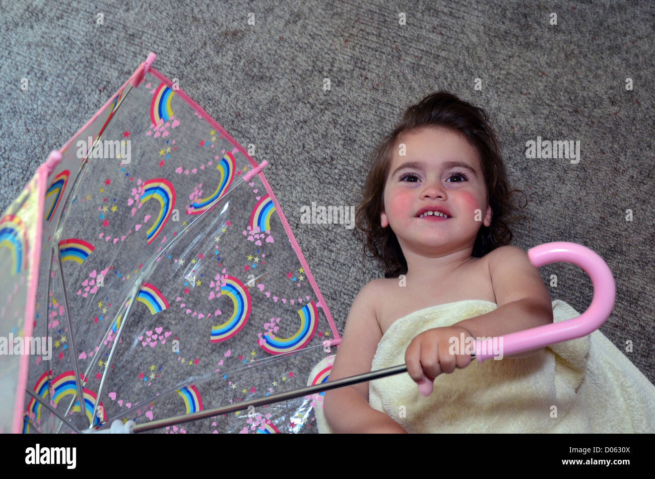 Little girl warped with a towel holds an umbrella after a shower. - Stock Image