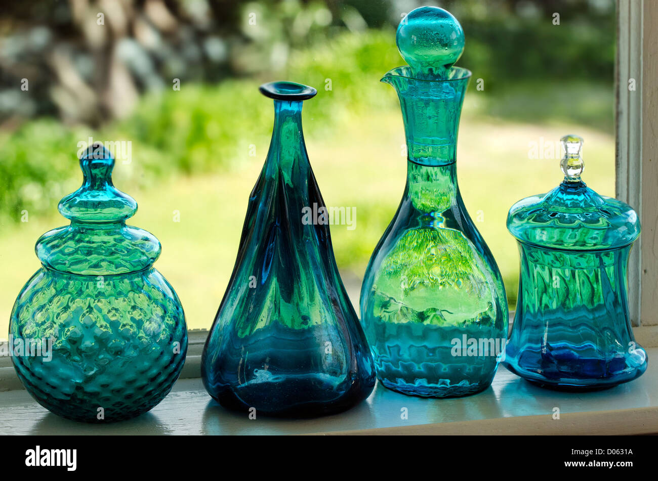 Unique green glassware on kitchen window. - Stock Image