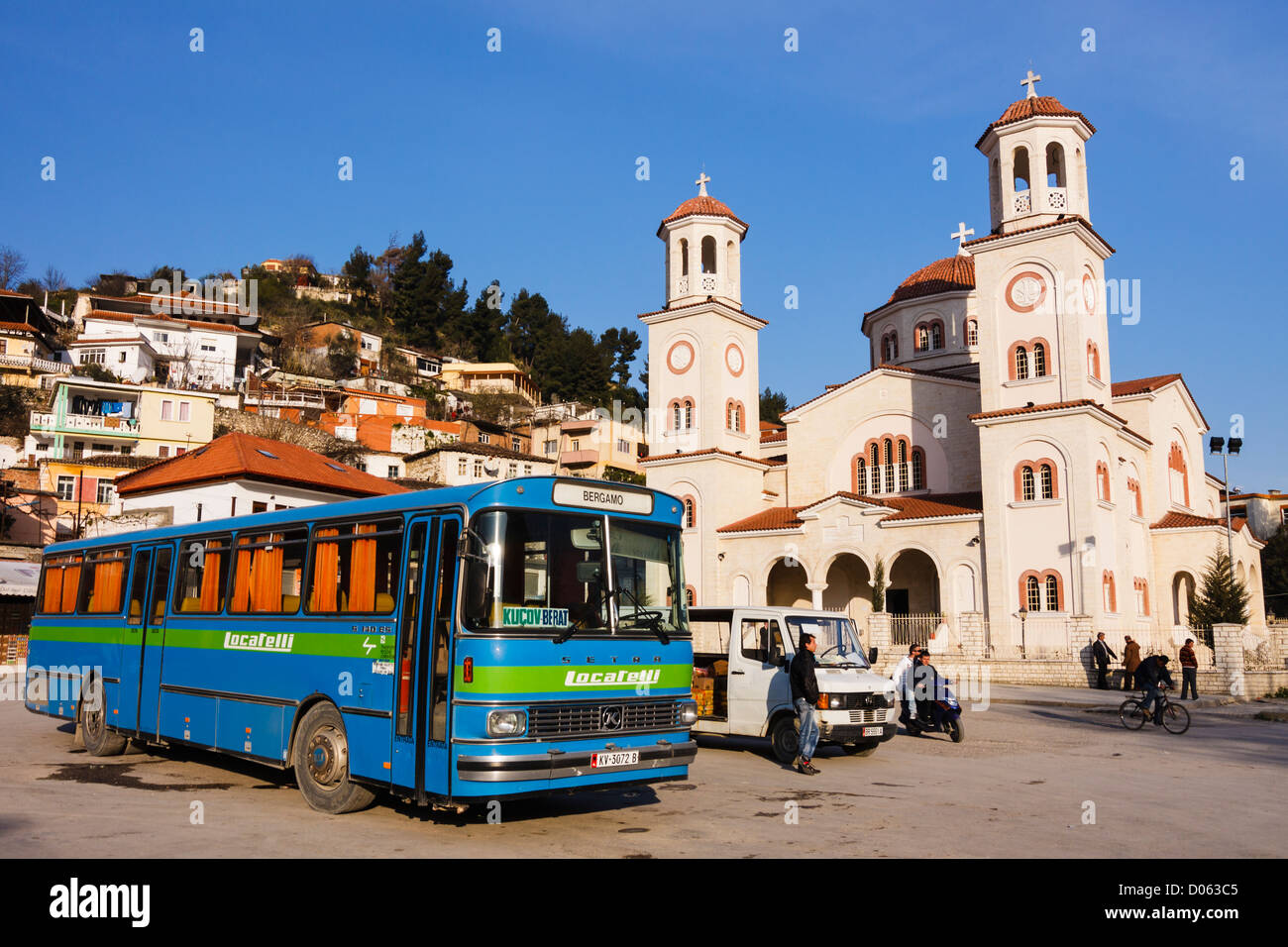 Orthodox Cathedral of St. Demetrius and bus stand with old coach. Berat Main Square, Albania - Stock Image