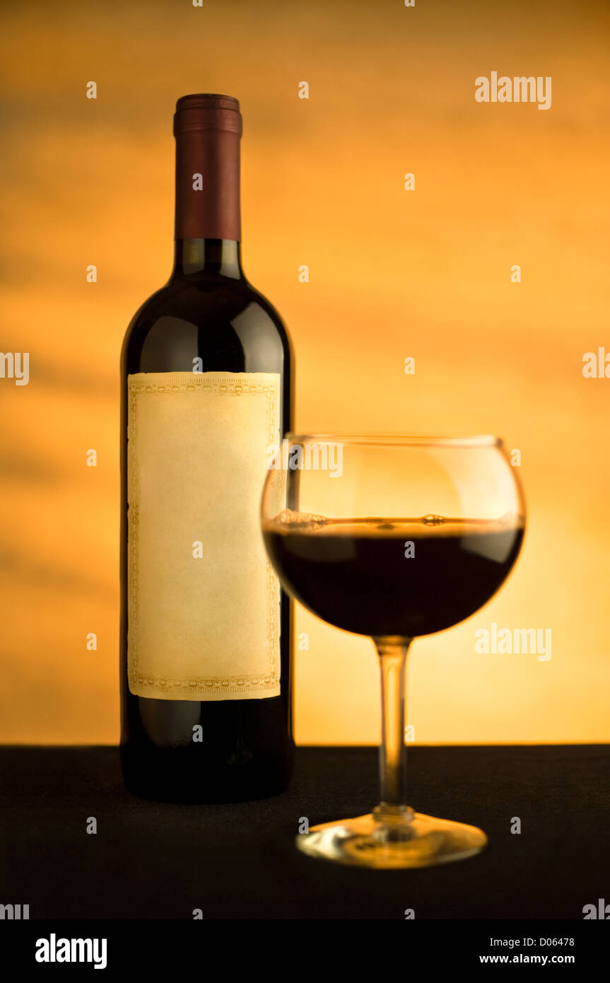 Wine glass and bottle with a warm glow in the background. No logo on bottle - Stock Image