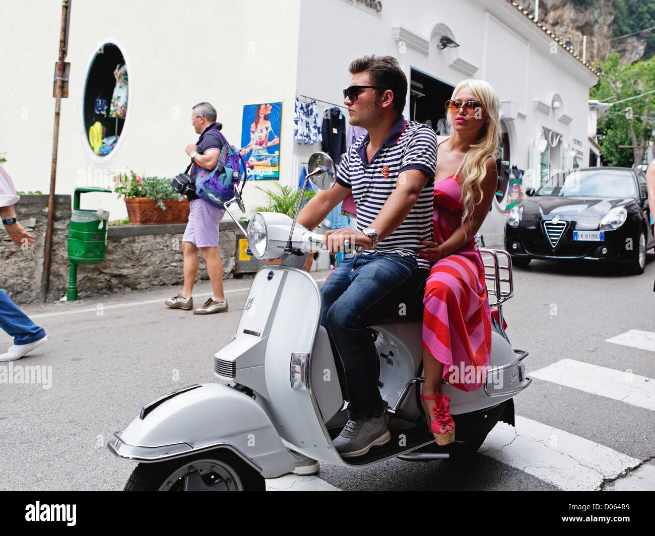 Young Couple Riding on a Scooter in Positano, Campania, Italy - Stock Image