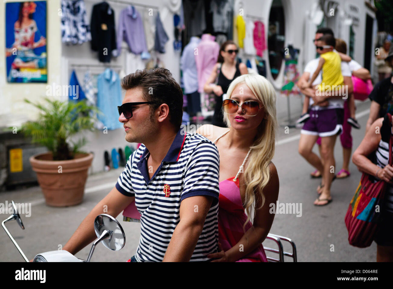 Young Couple Riding a Vespa Scooter on A street, Positano, Campania, Italy - Stock Image