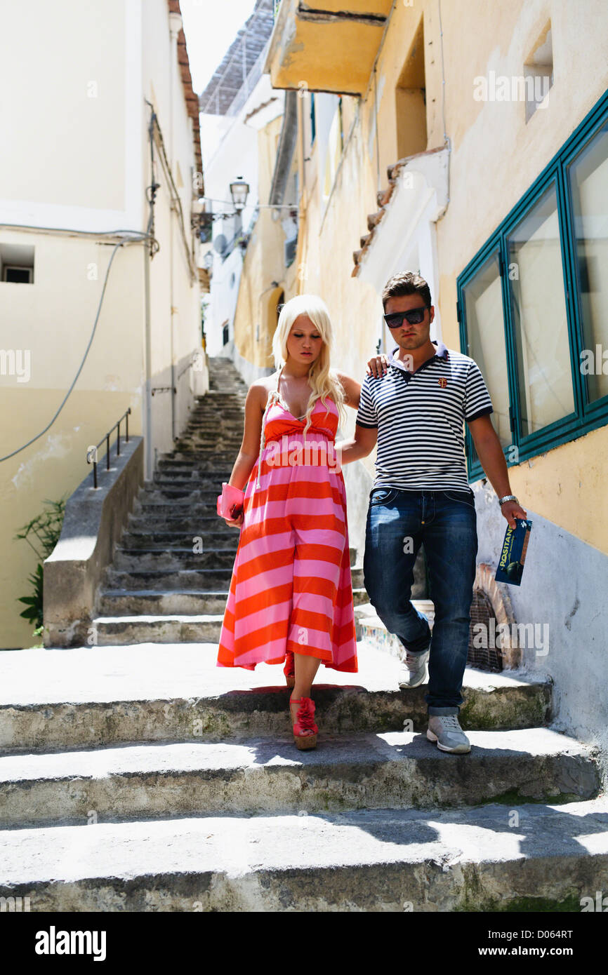 Young Couple Walking Down of Stairs in a Narrow Street, Positano, Campania, Italy - Stock Image