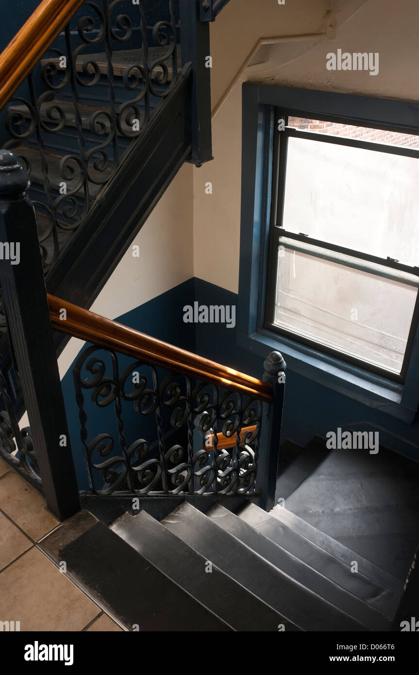 SIron and stone stairway in a century old New York City tenement - Stock Image