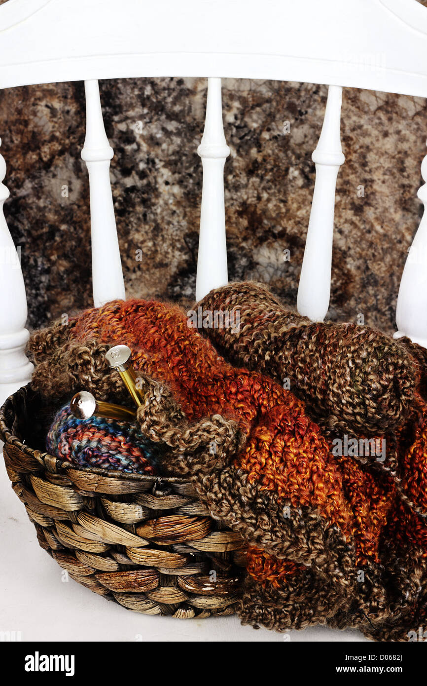 Basket filled with crocheted blanket, soft skeins of yarn needlework and knitting needles sitting on old antique - Stock Image
