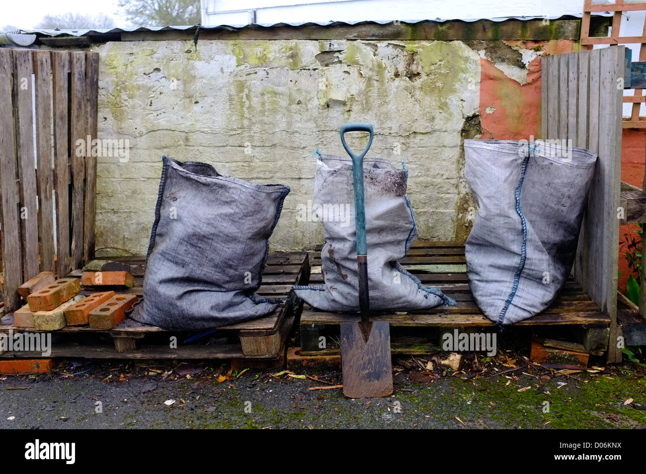 Three sacks of coal just delivered onto wooden pallets outside a house in Cornwall, UK - Stock Image