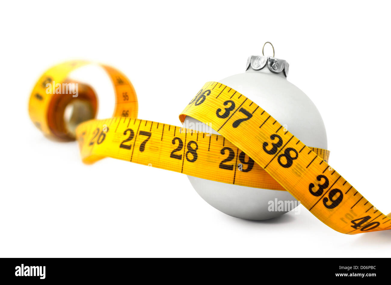 Tape measure around a bauble concept symbolizing Christmas weight gain from eating too much food. - Stock Image