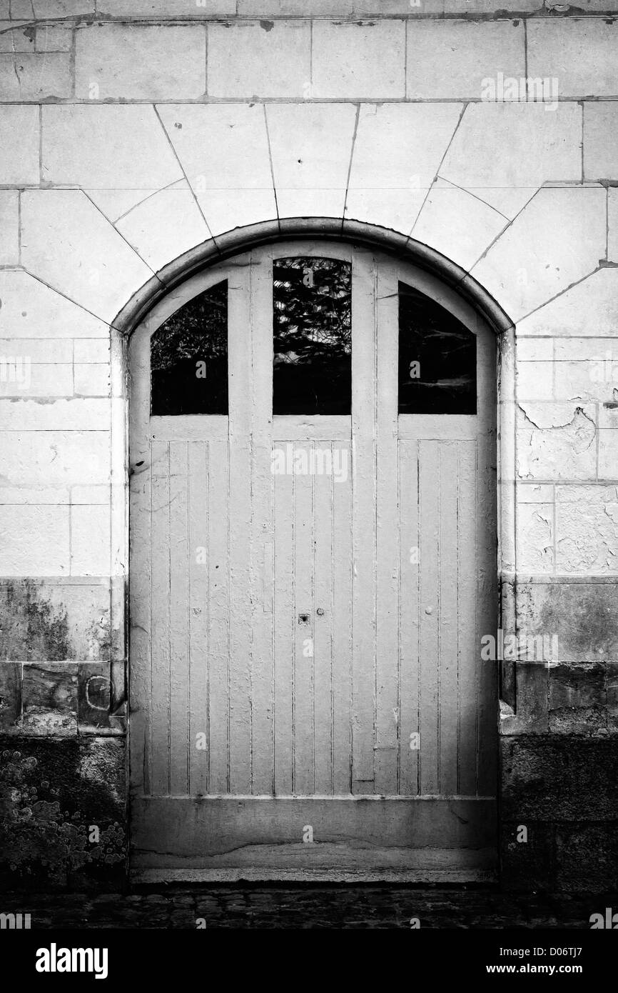 Black and white image of closed wooden door. - Stock Image