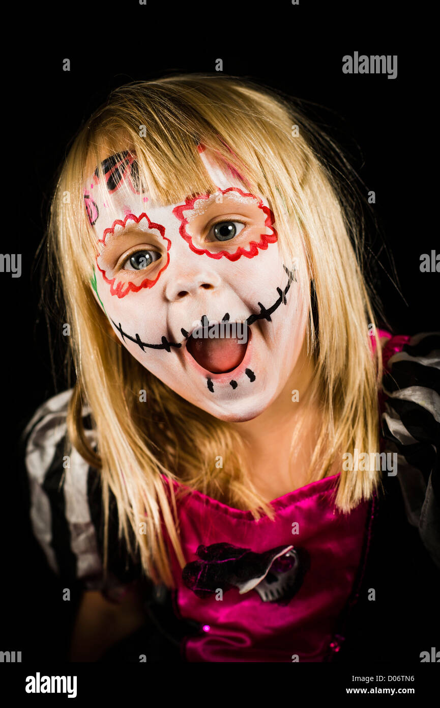 A young girl with face painted in Halloween theme style horror UK - Stock Image