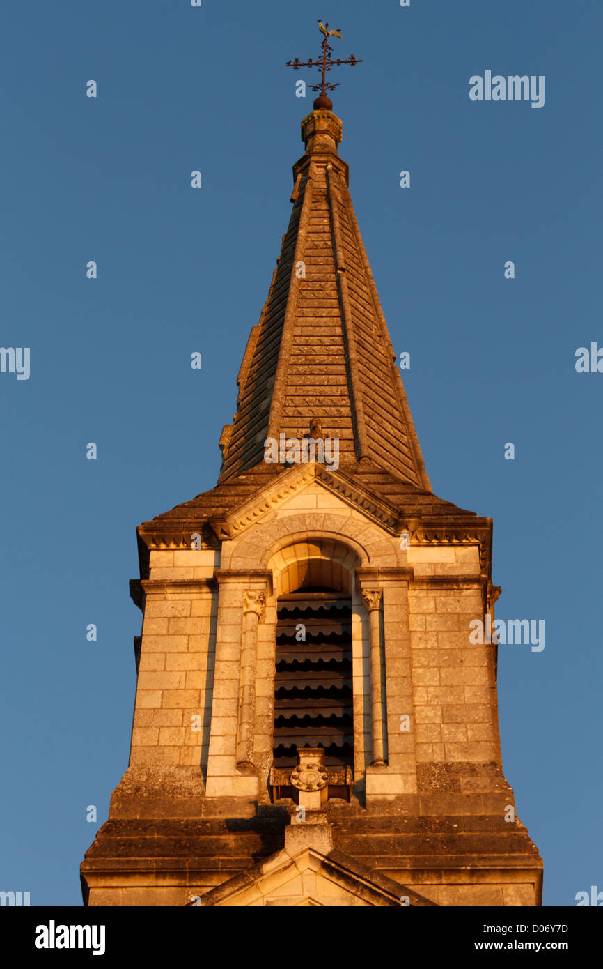 Sunlit church tower and spire. - Stock Image