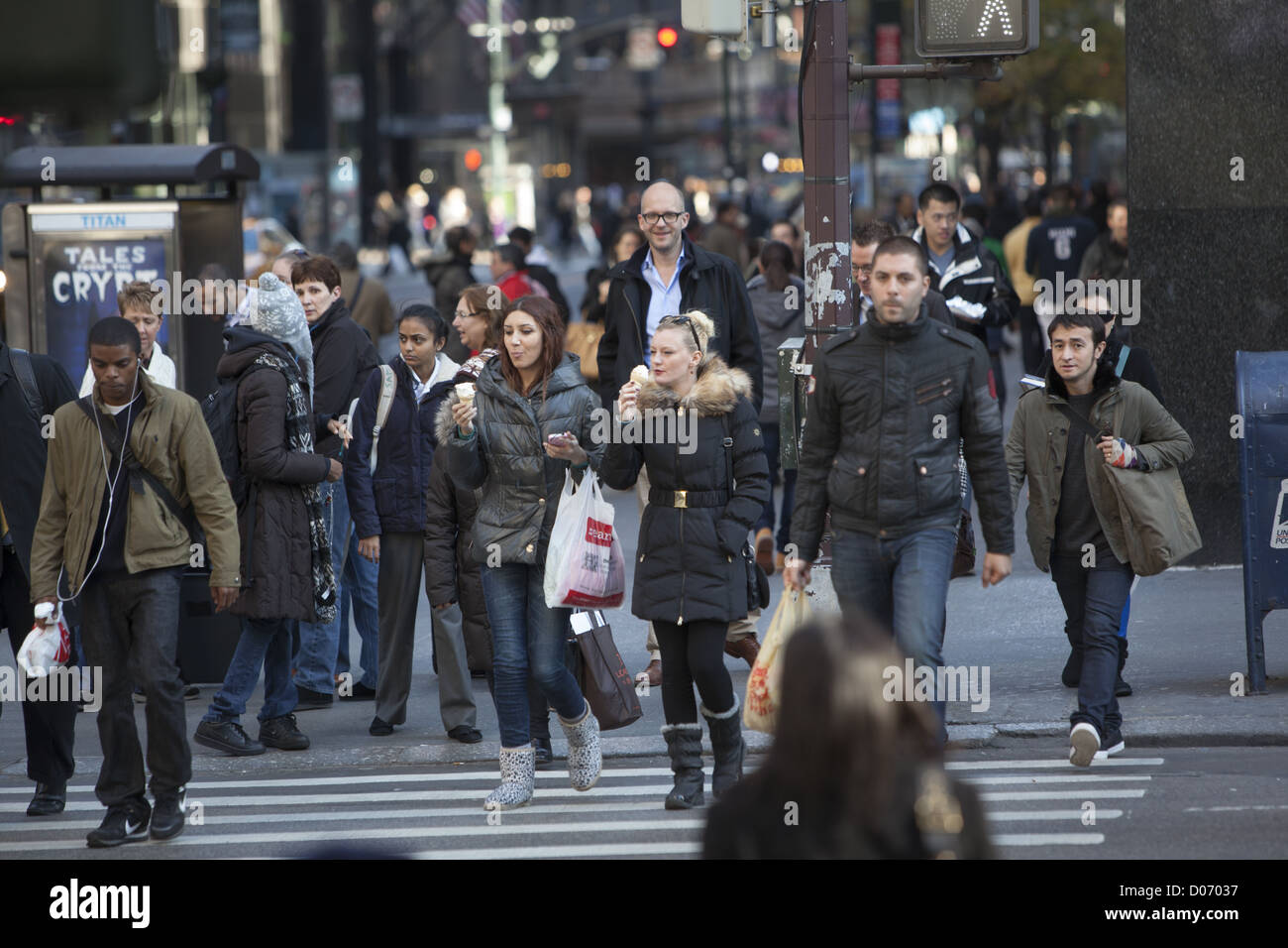 Women eat ice cream cones while crossing 5th Ave. on a brisk autumn day in Manhattan; NYC. - Stock Image