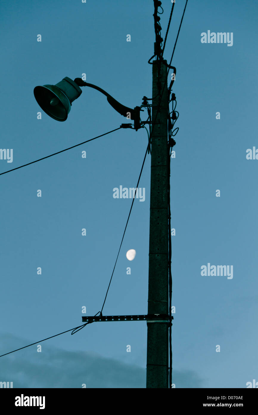 Telegraph pole at dusk with moon in sky. - Stock Image