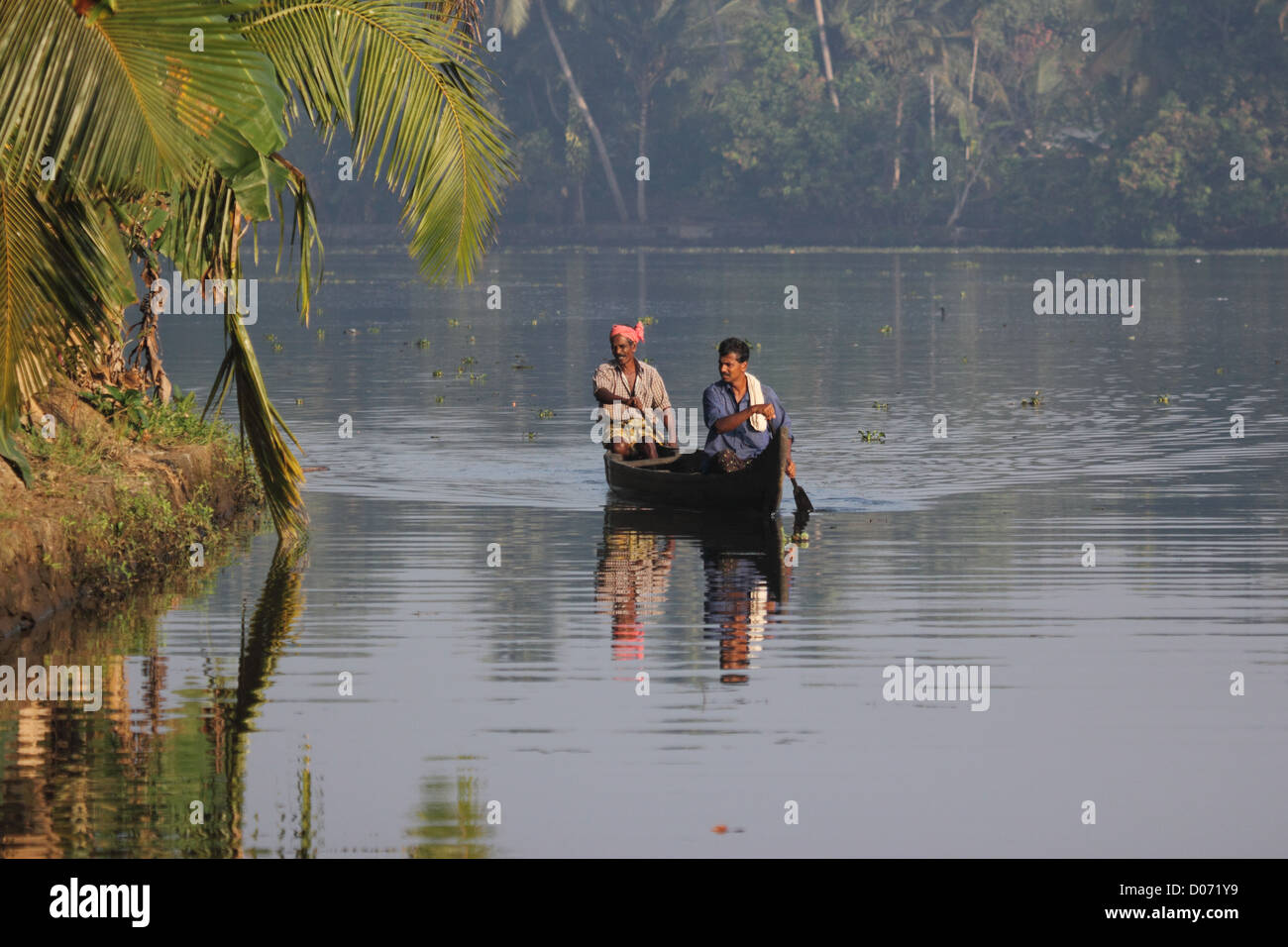 Two Keralites rowing across the backwaters in kerala. - Stock Image
