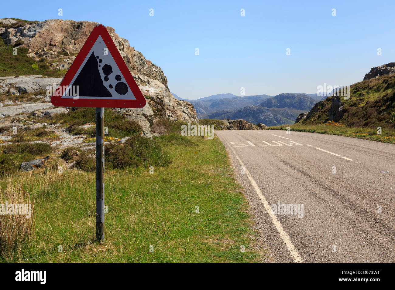 Triangular road sign warning danger of falling rocks in Wester Ross, Ross and Cromarty, Highland, Scotland UK, Britain - Stock Image