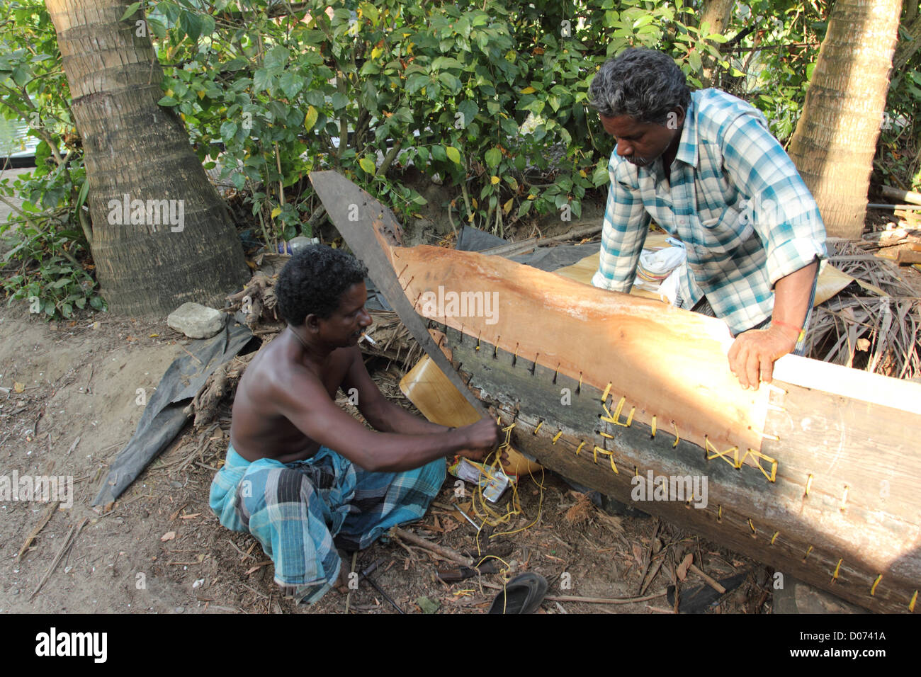 Man working on the process of building a boat. - Stock Image
