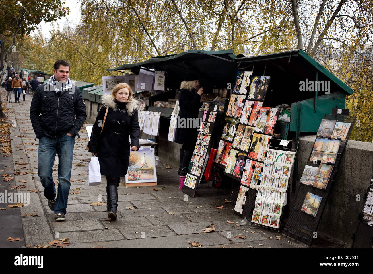 A man and a woman walk past art for sale on the banks of the River Seine , Paris - Stock Image