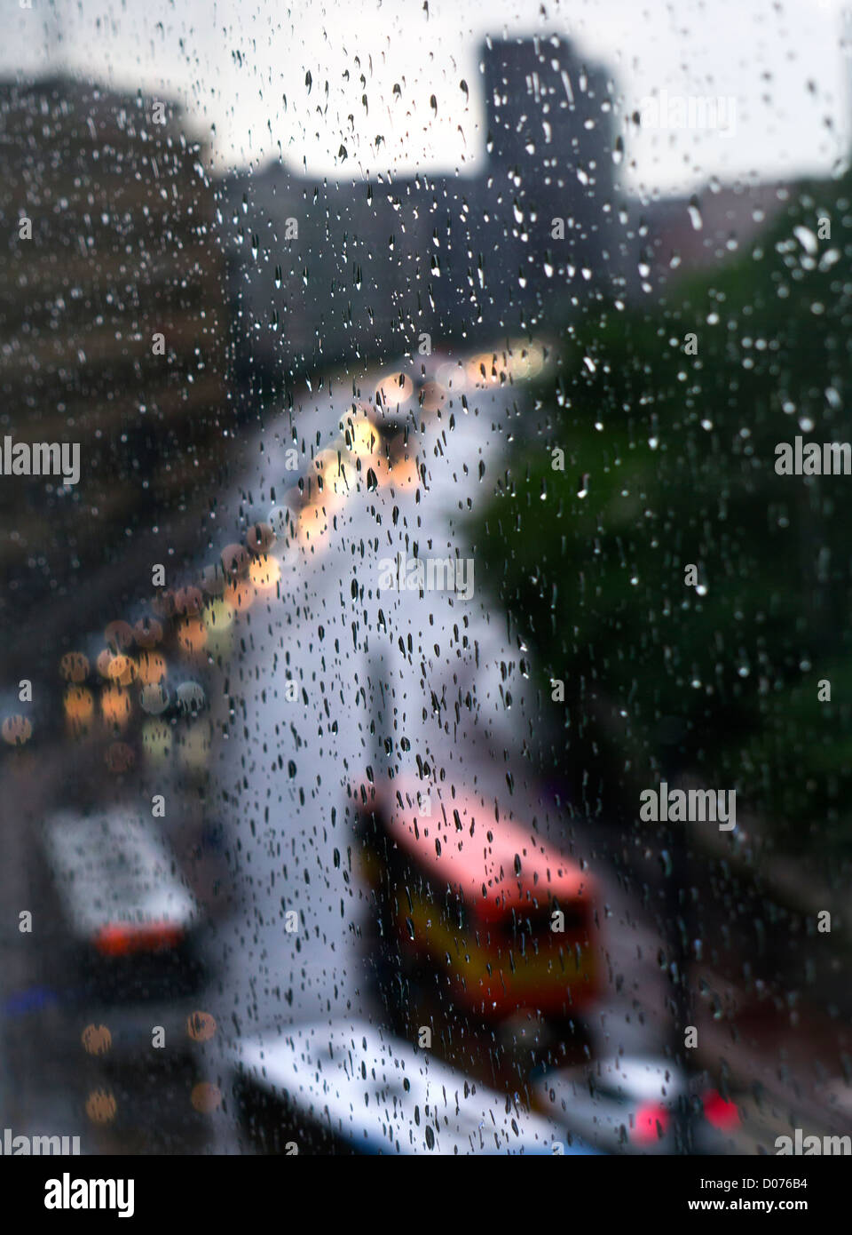 WINDOW RAIN CITY DEPRESSION FEAR OUTDOORS CONCEPT rain drops on high rise apartment block window with traffic flowing - Stock Image
