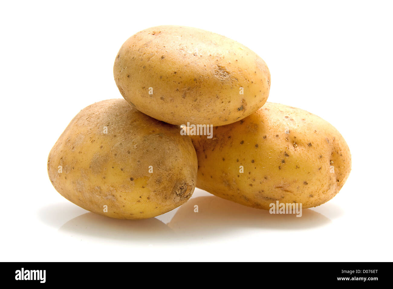 Stack of three unpeeled potatoes isolated on white background - Stock Image