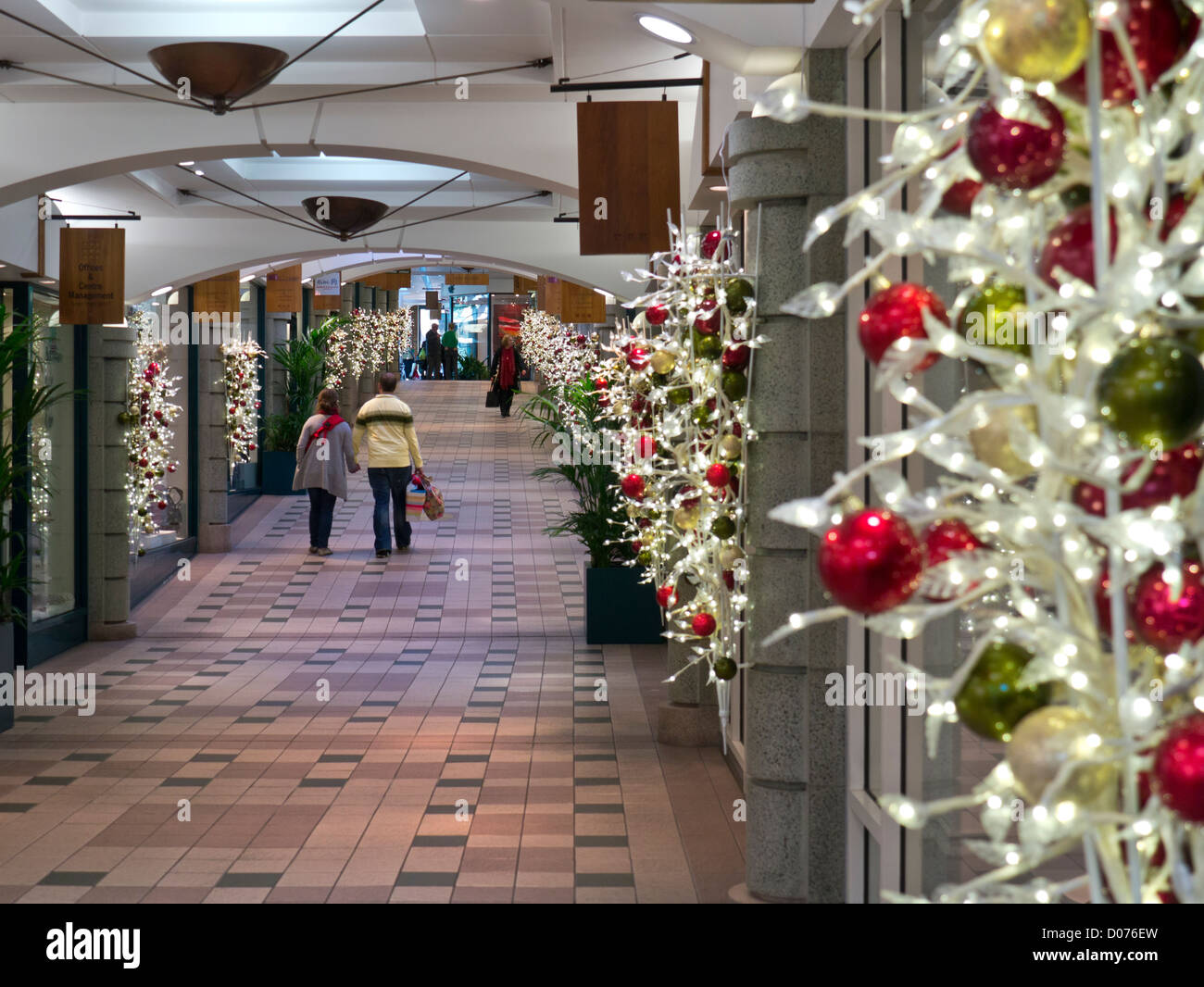 traditional christmas decorations with young couple carrying shopping bags in a quiet tunsgate shopping mall guildford