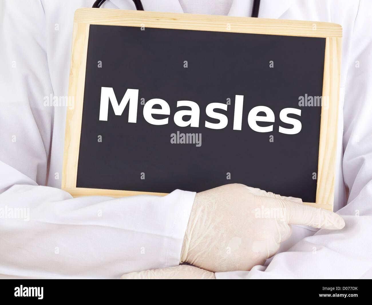 Doctor shows information on blackboard: measles - Stock Image