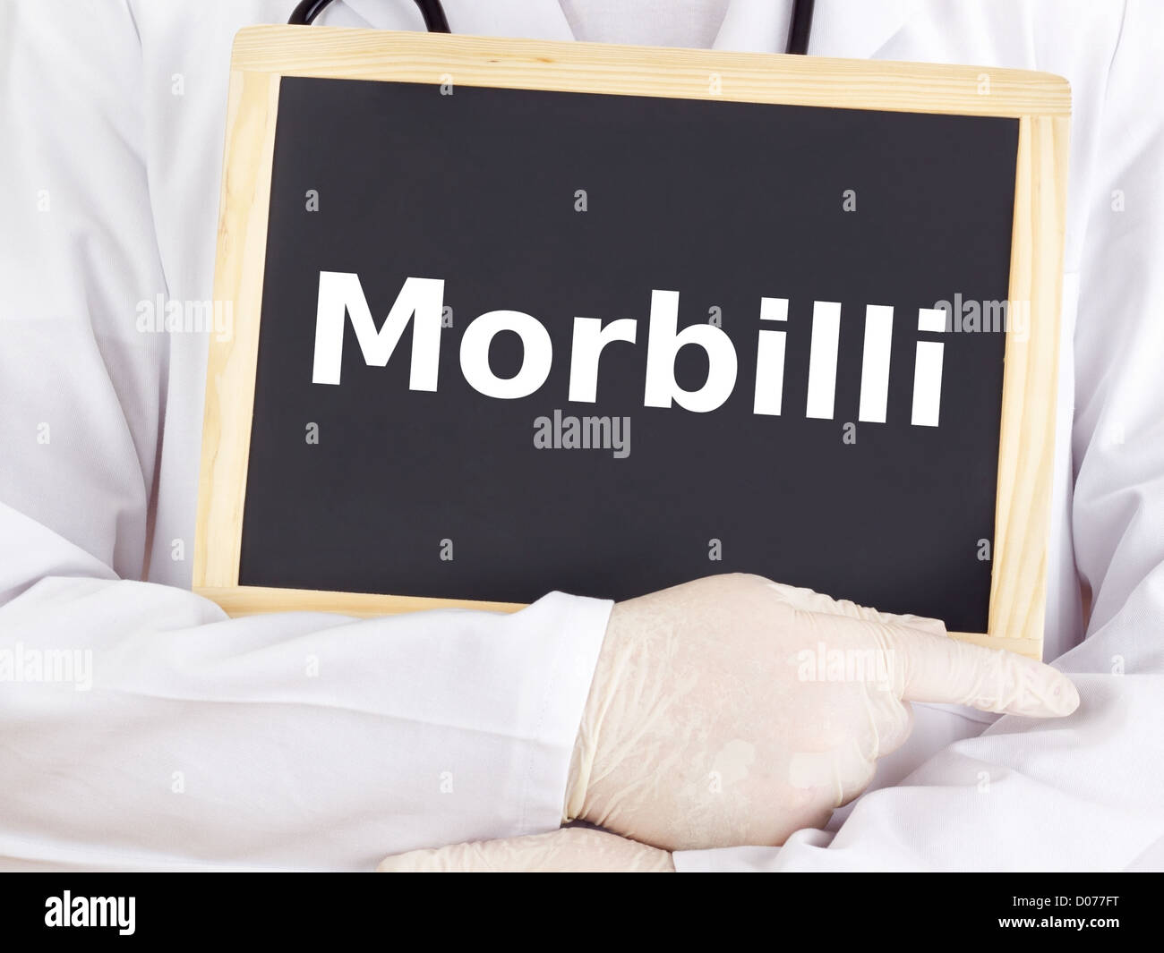 Doctor shows information on blackboard: morbilli Stock Photo