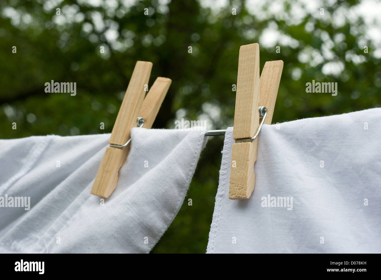 Clothes drying in the wind hanging on a clothesline held by pegs - Stock Image