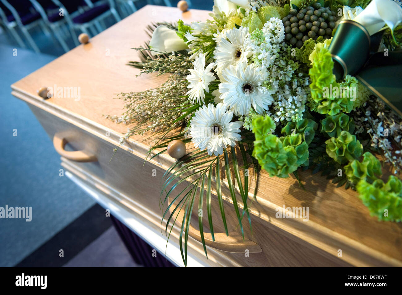 A coffin with a flower arrangement at a mortuary - Stock Image