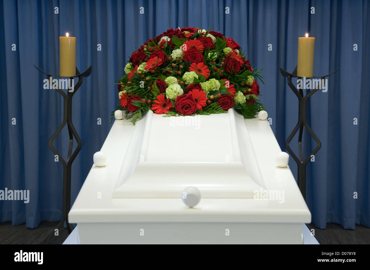A white coffin in a mortuary with a flower arrangement - Stock Image