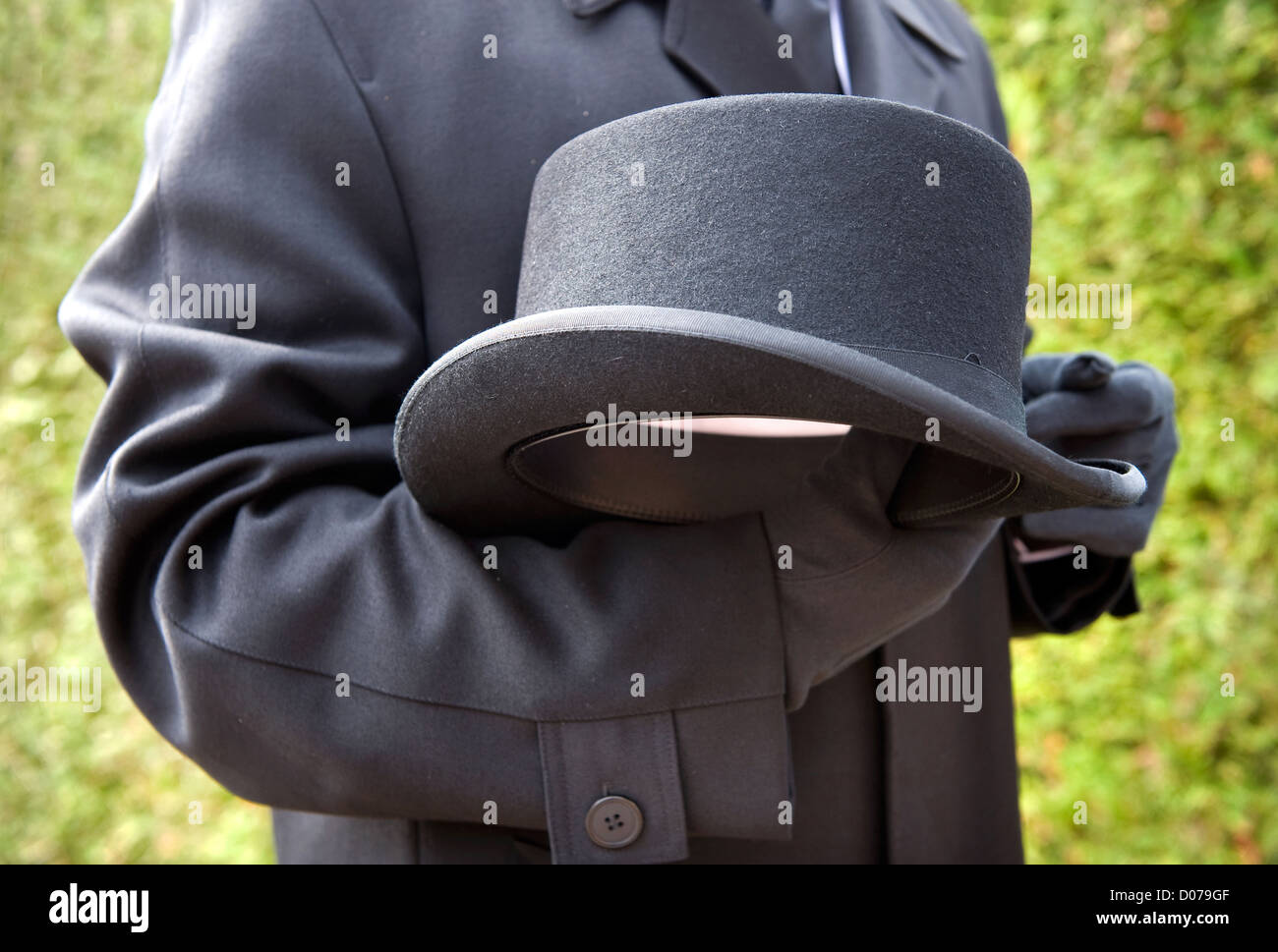 A funeral leader is respectfully carrying his hat - Stock Image