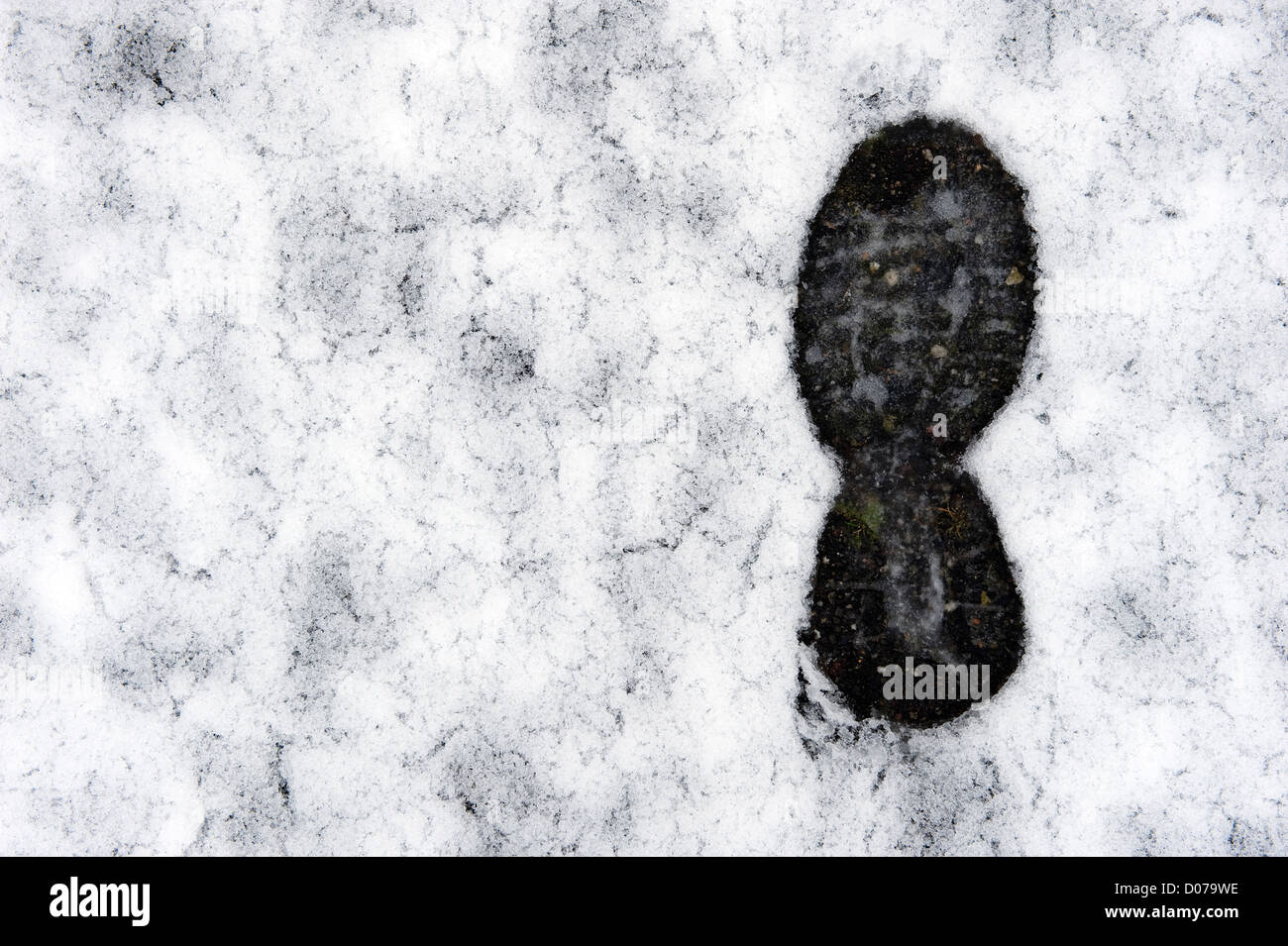 A single footprint in the melting snow - Stock Image