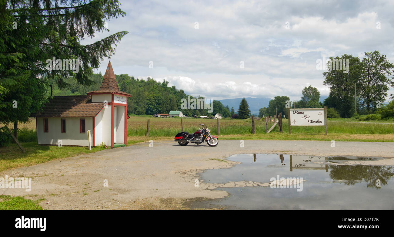 A motorcycle is parked by a small roadside church sanctuary in eastern Washington state, USA. - Stock Image