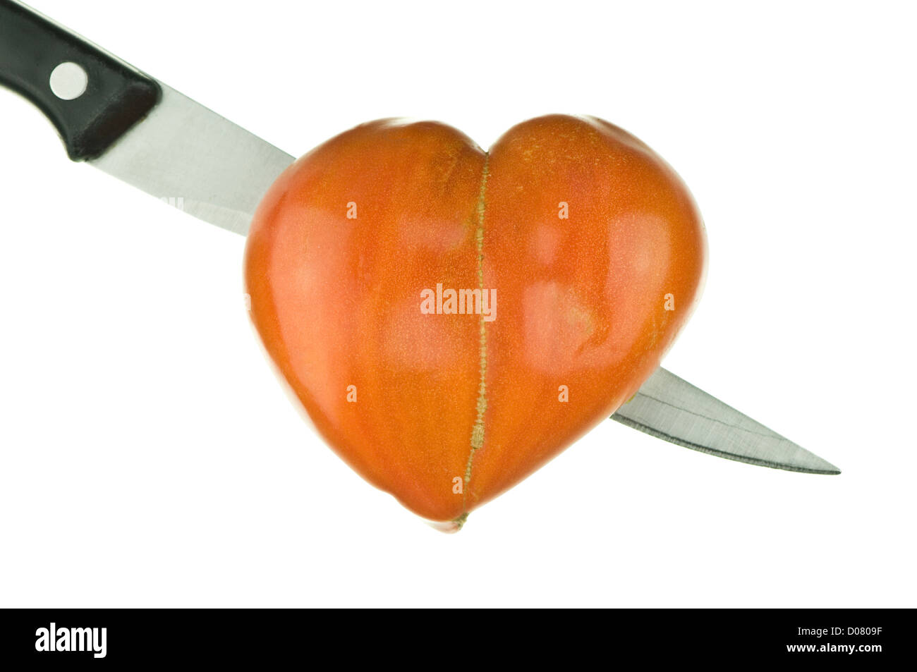 heart-shaped tomato pierced by a blade on pure white background - Stock Image