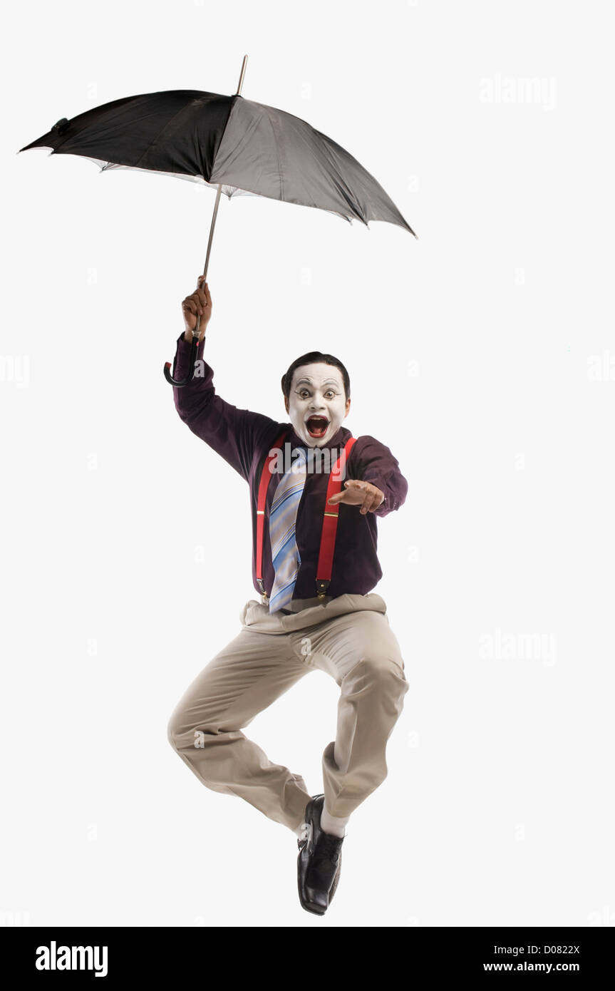 Mime falling with an umbrella - Stock Image
