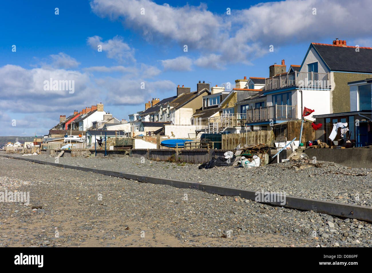 colourful coastal village houses at Borth mid Wales whose gardens back onto the beach, sea defenses, washing lines, - Stock Image