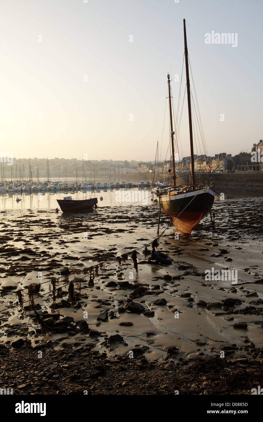 Low tide with sailing boat at rising sun in Camaret harbor Britanny - Stock Image