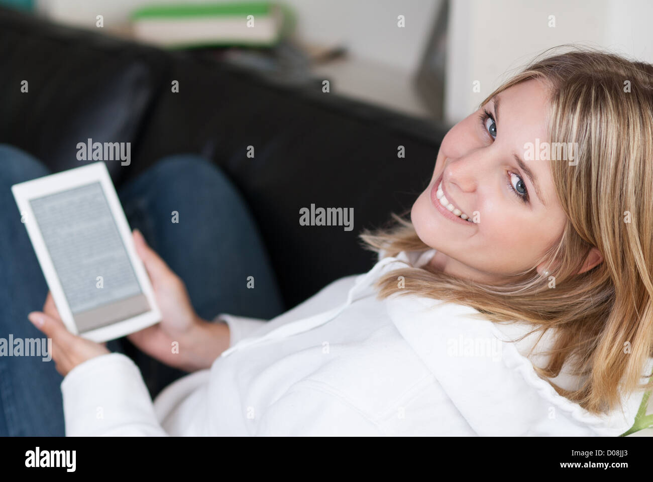 Young beautiful woman sits on a couch with an eBook Reader in her hands - Stock Image