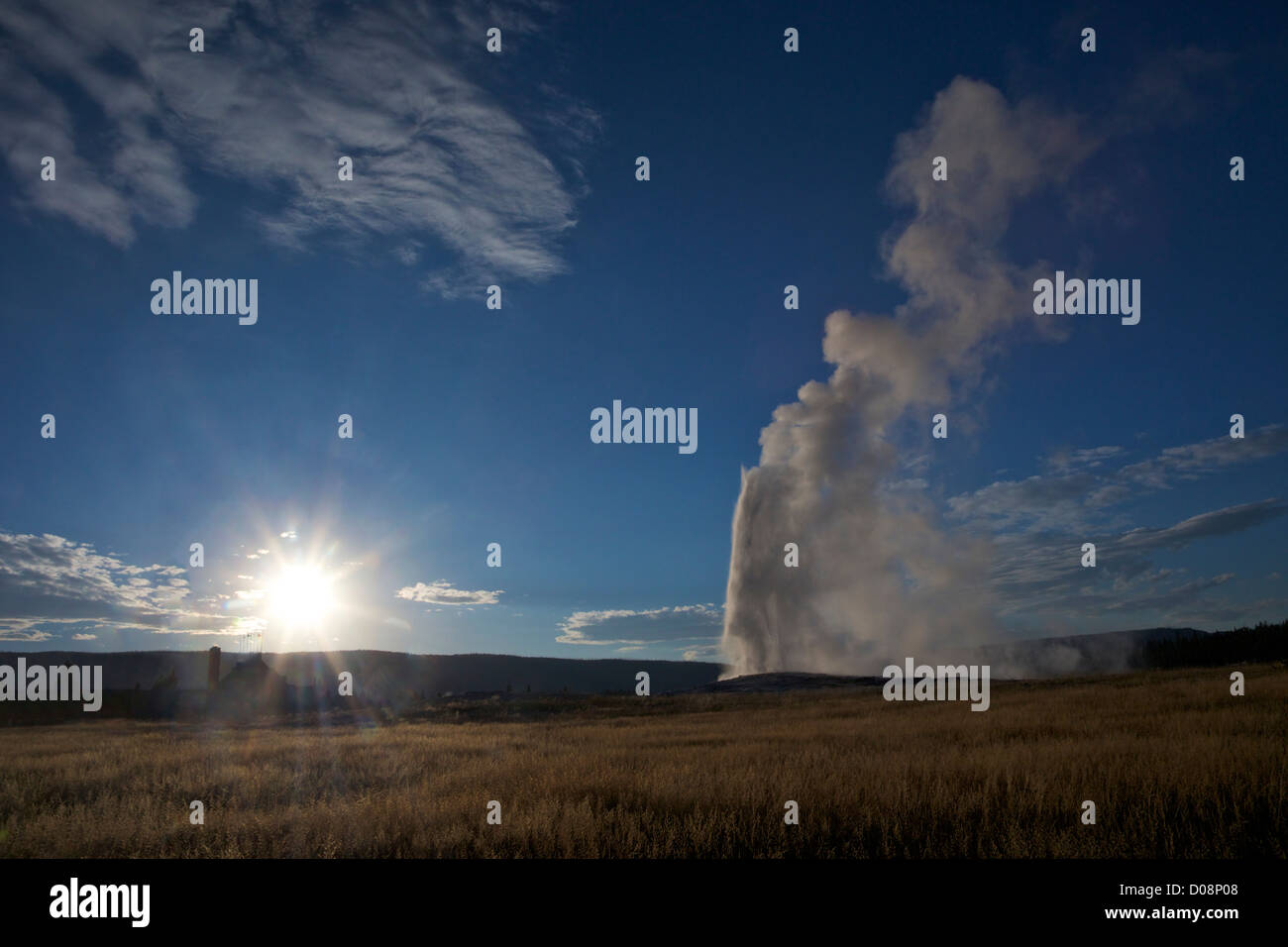 Old Faithful Geyser erupting in summer evening light, with Old Faithful Inn behind, Yellowstone National Park, Wyoming, - Stock Image