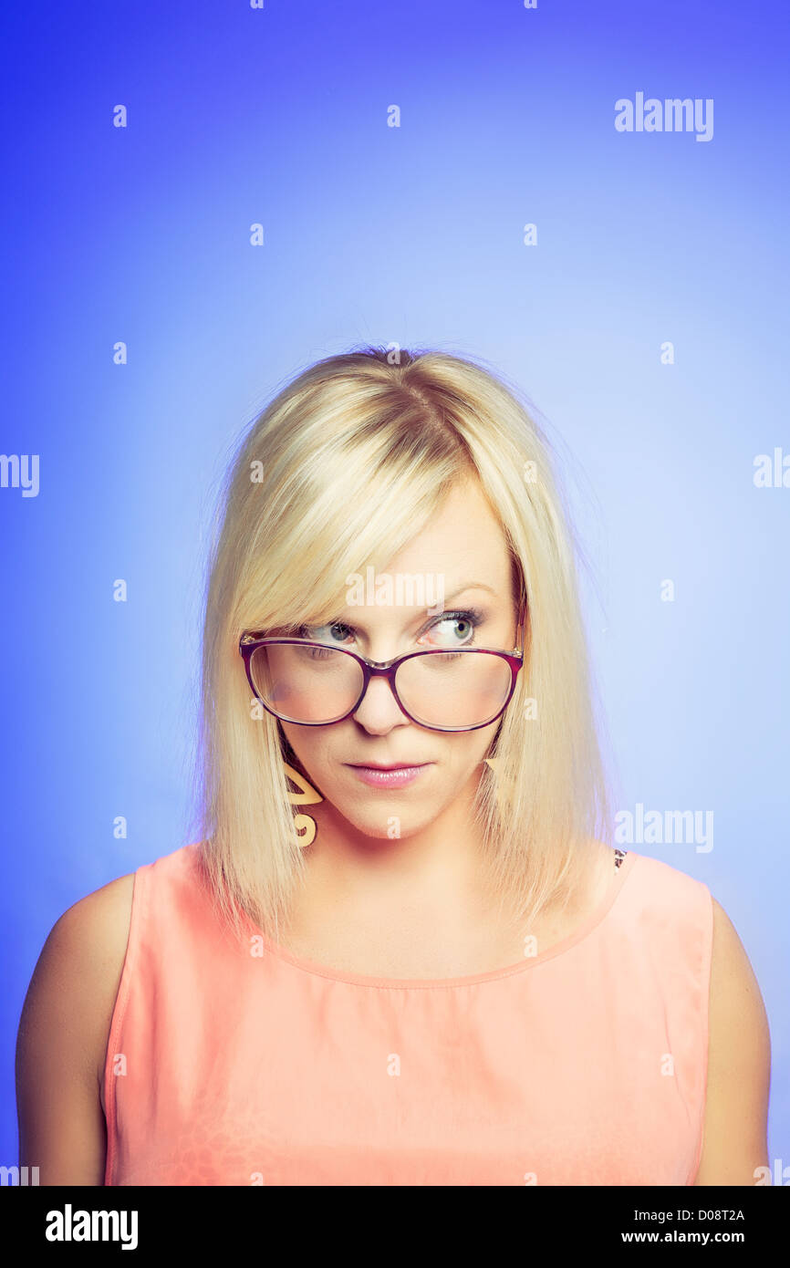 Portrait of a young skeptical woman isolated over blue background - Stock Image
