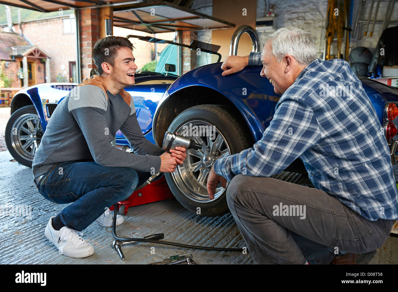 Father and teenage son working together in the garage on a for Ouvrir son garage auto