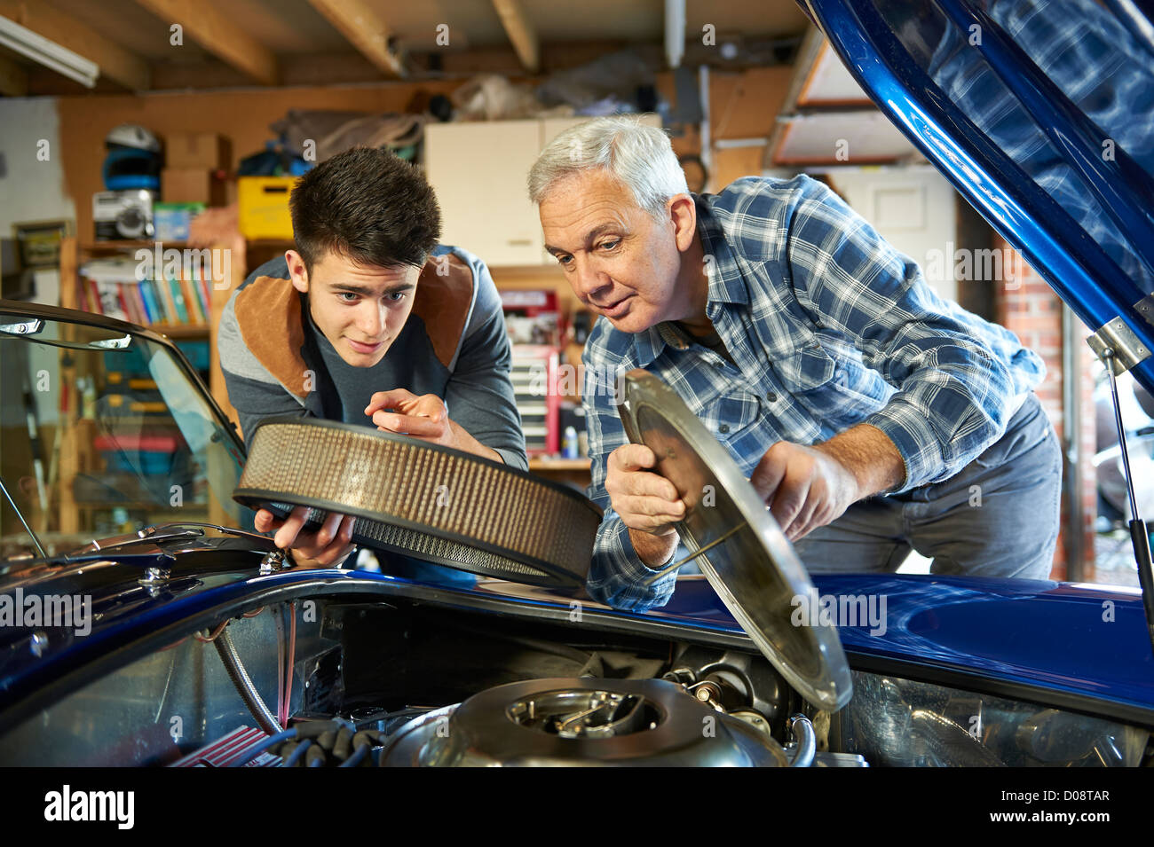 Father And Teenage Son Working Together In The Garage On A