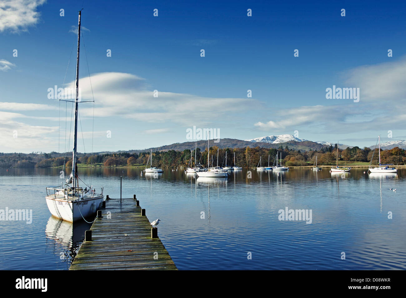 A yacht moored at a jetty in Waterhead, Ambleside on Lake Windermere in the Lake District National Park, England. - Stock Image