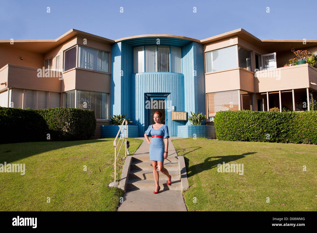 Girl In Front Of Retro Apartment Building